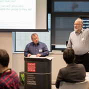 two members of Barod give a presentation in a conference room