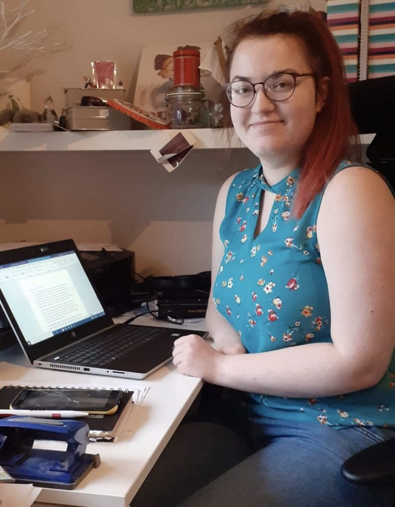 A photo of Emily sitting by her desk. Her laptop is open and there are a couple of books beside it.