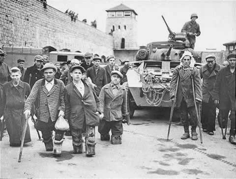 A crowd of wounded war veterans and other disabled people gathered beside an army tank. Tall walls enclose the space and a guard / watch tower is seen in the background