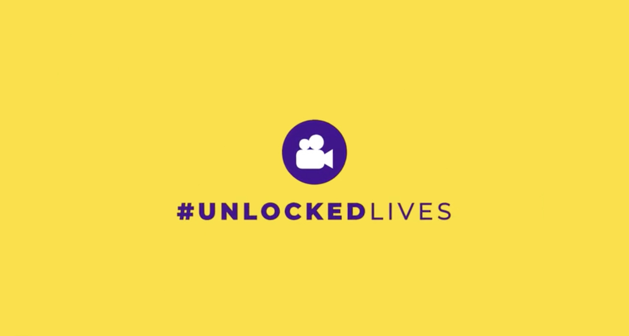 #UnlockedLives logo in black against a bright yellow background. The logo shows a white cartoon of a video camera set in a black circle with the project title in black writing underneath