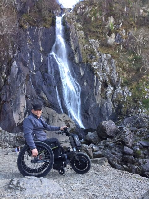 John on his hand bike in front of a waterfall amongst rocky surroundings